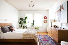 Um quarto tranquilo e agradável, com uma  cama de madeira simples e aerodinâmica. Em São Francisco, Califórnia, USA.  Fotografia: Ellie Arciaga Lillstrom.