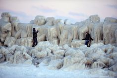 People walking at the frozen Black Sea near the ice-covered dam in Constanta, Romania.