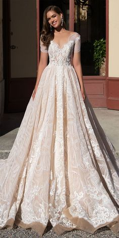 Luxurious wedding gown Brenda totally decorated with delicate lace and made of the finest nude gauze. Short sleeves and deep décolleté emphasize your beautiful neck. Hem falls to the floor. The back of the dress is beautifully buttoned up making accent on your slim waist.