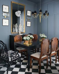 Charcoal blue walls with gold accent pieces, antique chairs & modern table