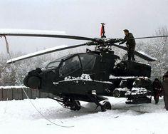 Unos soldados estadounidenses retiran la nieve de un AH-64A Apache en una base de la SFOR en Bosnia y Herzegovina, 16 de diciembre de 1997.