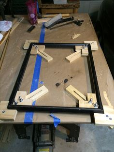 This is a set of adjustable framing jigs I made to try to better align the pieces while the glue dries.  They aren't perfect but help keep things square.  The downside is that you must keep the glue off the jigs or they might become part of the frame so I insert newspaper in the jig to prevent that.