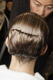 Vogue: Spring/Summer 2015 Backstage Beauty | Alexander McQueen - Hair, by Guido Palau was slicked into folded, wet-look chignons.