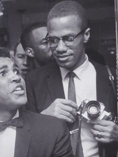Black Muslim leader Malcolm X teasingly leaning on shoulder of tuxclad Cassius Clay who is sitting smugly at soda fountain counter surrounded by. Malcolm X, Black History Facts, Black History Month, Black Power, Muhammad Ali Boxing, La Ilaha Illallah, By Any Means Necessary, Black Pride, African History