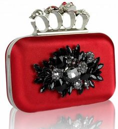 This red clutch bag is packed full of attitude with its knuckle skull display and black floral crystal decoration. The black and red combination of the bag and crystals go hand in hand and looks superb when matched with your evening outfit.