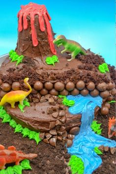 Homemade Dinosaur Birthday Cake a dinosaur birthday cake with chocolate frosting, a volcano, a blue frosting waterfall, and toy dinosaurs on a blue background Dinosaur Cakes For Boys, Make A Dinosaur, Dinosaur Birthday Cakes, 4th Birthday Cakes, Dinosaur Party, Girl Birthday, Birthday Ideas, Blue Frosting, Chocolate Frosting
