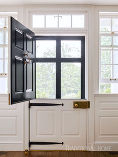 Look at this! I have never loved a door more! I have never seen one flanked by double hung windows. The brass box lock and the strap hinges are nice period details. via