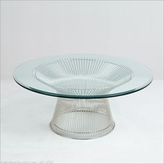 Part of the Platner Collection, the Coffee Table features thick tempered glass resting on a sculptural base of stainless steel rods, which resemble a shiny sheaf of wheat. Platner designed both the structure and the production method for these designs, forming his primary contribution to the mid-century modern furniture movement and is still an enduring icon of 1960's Modernism.