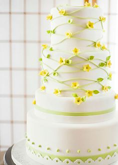 A modern interpretation of yellow jasmine and spring green vines highlight this awesome cake by Flower & Flour.