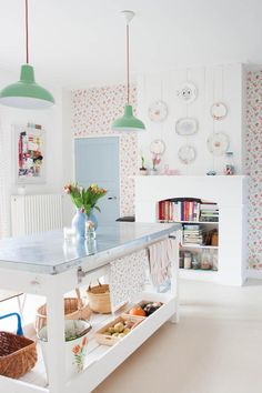 20 Ways to Decorate With Flowers For Spring - feminine kitchen design with mini floral wallpaper, teal drop lighting, a stainless steel island, weaved baskets for storage, + modern white fireplace