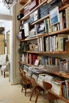 Designer John Derian's home is photographed for Madame Figaro on February 3, 2015 in New York City. The hallway-library connects the living room to the entrance. On the shelves, the designer combines piles of books, paintings, handwriting and memory boxes. PUBLISHED IMAGE.