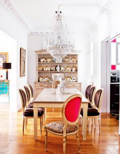 Dining room with white walls, large chandelier, wood floors, wood dining room table, wood chairs with patterned fabric, and wood built-in unit