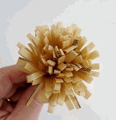 Flores de papel reciclado  1.-Doblas el papel y lo cortas en tiritas, sin llegar a al doblez del papel.  2.-Una vez lo hayas cortado, lo enrollas formando una flor y lo grapas.  3.-Puedes hacer las flores como te guste, según el color del papel que elijas.  Ideales para adornar un regalo.