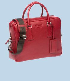 Travel in style with this sleek nylon travel tote from Prada.