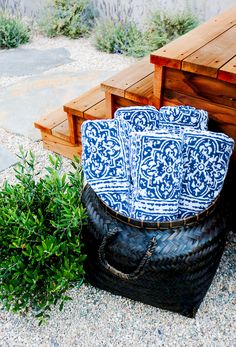 Wood staircase, black woven basket, and printed blue towels