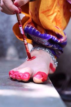 A dancer in India applying alta (red color) on her feet to get ready for her performance.