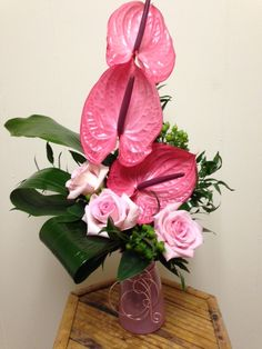 Who doesn't love pink?  Pink anthurium and pink roses with lush greens by Merritts Flowers, Pitman, NJ.