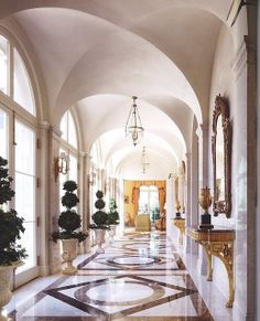 Elegant hallway filled with gilt tables, manicured topiaries and a beautiful inlaid floor.