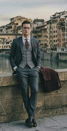 - with a dapper combo with a gray waistcoat gray suit navy red striped silk tie white spread collar shirt brown overcoat black leather boots red silk pocket square Dapper Suits, Mens Suits, Casual Wear For Men, Classy Men, Elegant Outfit, Black Leather Boots, Gentleman Style, Mens Fashion, Fashion Trends