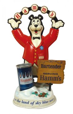 """Sold For $130 in 2012  Breweriana display figure, Hamm's, plastic w/cdbd """"Bartender Serving Hamm's"""" sign & """"New All Aluminum"""" can w/open top, colorful graphics including bottle cap lettering arch, slight cracks at base & cdbd has been taped, VG cond, 16.75""""H x 10""""W x 7.75""""D."""