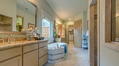 A stunning master bedroom retreat with large closet and soaking tub by Darling Homes at Mustang Park in Carrollton. #new #home #bathroom #marblebathtub