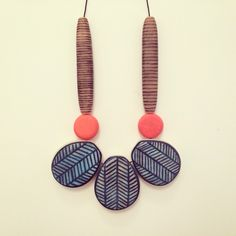 Blue and white herringbone on teardrop shaped bead. Hand sculpted and painted polymer clay jewellery made by Nellsdottir