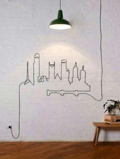 Aqui, o que virou arte não foi exatamente a luminária, e sim, seus fios que formam o desenho de uma cidade. Para fazer igual é só pensar em um projeto e utilizar grampos de arame ao longo da parede para dar forma aos fios. A ideia veio daqui.