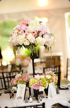 I like the idea of a tall centerpiece with similar, smaller arrangements around it.