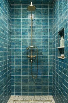 Speckled blue-green shower tiles give this space texture and color. Design by Mia Rao Design. #tile #tiledbathroom #greenbathroom #bluebathroom #showertile