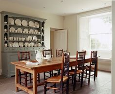 Irish country kitchen with limestone floor, window seat, farmhouse table, and antique hutch.