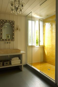 Love this bathroom with a yellow tiled wet room shower, and ornate lighting .  @thedailybasics  ♥♥♥