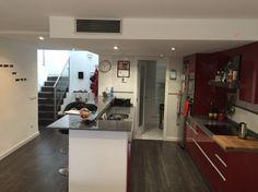 Tras su reforma cocina abierta al salón de estilo moderno en tonalidad roja