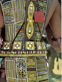 """Africa   'Modern motifs' find increasing use in the eclectic designs of Wodaabe fashion.  Blanket labels blend with embroidery on a male dancer's tunic.  Eyelets festoon his ammunition belt, worn strictly for decoration   Page 504, National Geographic October 1983, 'Niger's Wodaabe:""""People of the Taboo""""; article and photos by Carol Beckwith."""