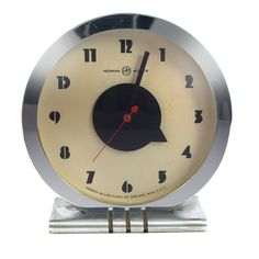 Gilbert Rohde Art Deco table clock, by Herman Miller, 1930s, round chromed metal case, stainless base
