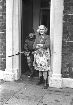 Soldier shelters in the doorway of a house in the Markets area of Belfast during a British Army search following the escape of internees from the prison ship Maidstone. The elderly lady resident appears unconcerned having seen it all before. NI Troubles. Ref: 19720119004. Copyright Image from Victor Patterson, 54 Dorchester Park, Belfast, UK, BT9 6RJ..Tel: +44 28 9066 1296.Mob: +44 7802 353836.Voicemail +44 20 8816 7153.Skype: victorpattersonbelfast.Email: victorpatterson@mac.com.Email: ...