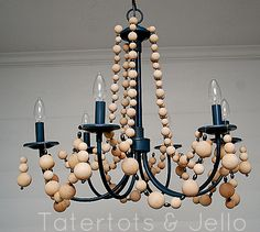 super cheap & easy, diy wood bead chandelier... Would also be pretty with the balls painted all white or different colors!