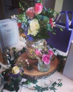 Perfect centrepiece for an Easter wedding...Log base placed on top of ivy with a colourful array of flowers surrounded by chocolate mini eggs!
