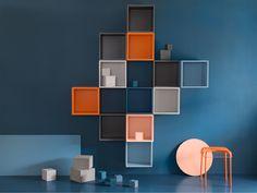 Un mur bleu avec des cubes en gris, orange et bleu.