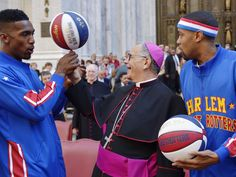 Bull Bullard, left, of the Harlem Globetrotters, twirls a basketball with Bishop Dominick J. Lagonegro, center, as teammate Cheese Chisholm watches, during the 71st annual Columbus Day parade in New York. Lagonegro is the Auxiliary Bishop of the Archdiocese of New York.   Porter Binks, EPA