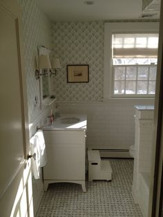 Sister Parish chou chou wallpaper, waterworks vanity, gray basketweave floor, white subway tile, linen sconces