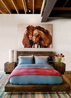 Rustic and simple bedroom with horse art and high ceilings.