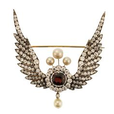 This beautiful brooch of winged design features a cabochon garnet framed by diamonds and flanked at the top and bottom with lustrous pearls. The detail can be seen in the wings meticulously set with old European-cut diamonds. Together with its original fitted box. English, late 19th century