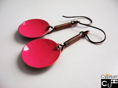These cheerful, coloured earrings are entirely handmade. The disc is hand-forged from raw copper and made slightly concave. Frontal side is enamelled in pink, while external side is patinated and satin finished. This coloured pendant is held up by a spring of copper wire. This pair of earrings may be produced on demand in many other colours.