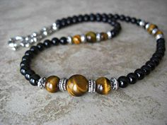This casual and stylish mens necklace is carefully handmade by me, featuring genuine Black Onyx round beads and natural semi precious Tiger Eye stone beads in nice amber luster. This necklace is studded with lead safe antique silver tribal styled tube spacers and beads. The necklace