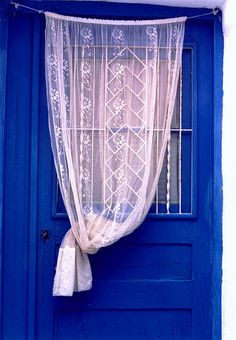 Blue wooden door with white embroidered curtain in a Greek village / by Marite2007, via Flickr