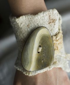 Nuno felted cuff. Beautiful button feature. Felt looks primitive and feral; naturals with silk perhaps?