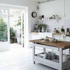 white brick tiles wood counters over distressed white cabinets