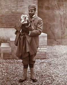 King George of England holding his dog with scarf on. Vintage photo.