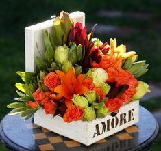 Liliums, rosas, lisianthus, leucadendron en caja personalizada.