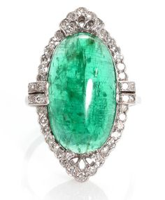 A cabochon emerald and diamond platinum ring, circa 1920 elongated oval-shaped emerald cabochon measuring approximately: 18.5 x 10.8 x 4.2mm; mounted in platinum.
